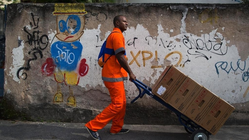 A city worker pushes boxes of electronic voting machines to a voting center ahead of tomorrow's elections in Rio de Janeiro, Brazil, Saturday, Oct. 25, 2014. Brazilians will go to the polls on Sunday to decide who'll be the next leader of Latin America's biggest economy. (AP Photo/Leo Correa)