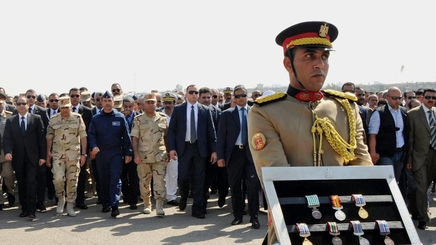 Oct. 25, 2014: In this photo provided by Egypt's state news agency MENA, Egyptian President Abdel-Fattah el-Sissi, far left, and other officials follow a soldier carrying medals of troops killed in Friday's assault in the Sinai Peninsula, during a military funeral in Cairo, Egypt.  (AP/MENA, Sheriff Abd el-Moneim)