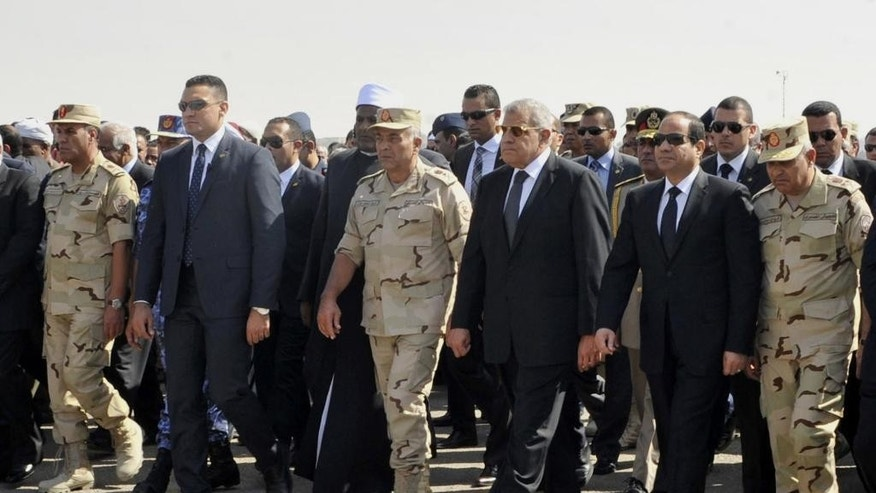 Oct. 25, 2014: In this photo provided by Egypt's state news agency MENA, Egyptian President Abdel-Fattah el-Sissi, second right, and other officials follow a soldier carrying medals of troops killed in Friday's assault in the Sinai Peninsula, during a military funeral in Cairo, Egypt.  (AP/MENA, Sheriff Abd el-Moneim)