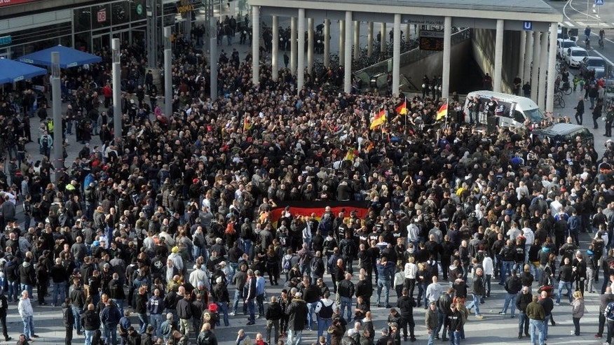 Far-right demonstrators  gather in Cologne, Germany,  Sunday Oct. 26, 2014. A demonstration by German far-right groups has erupted into violence in the heart of the western city of Cologne. Police say they are using water cannons and pepper spray in an attempt to calm the situation after protesters threw bottles and fireworks at officers. Police spokesman Andre Fassbender says there are no figures on injuries or arrests yet. Some 2,000 people attended the demonstration Sunday directed against Islamic extremism. It was organized by neo-Nazi groups and members of Germany's football hooligan scene.  (AP Photo/dpa,Caroline Seide)