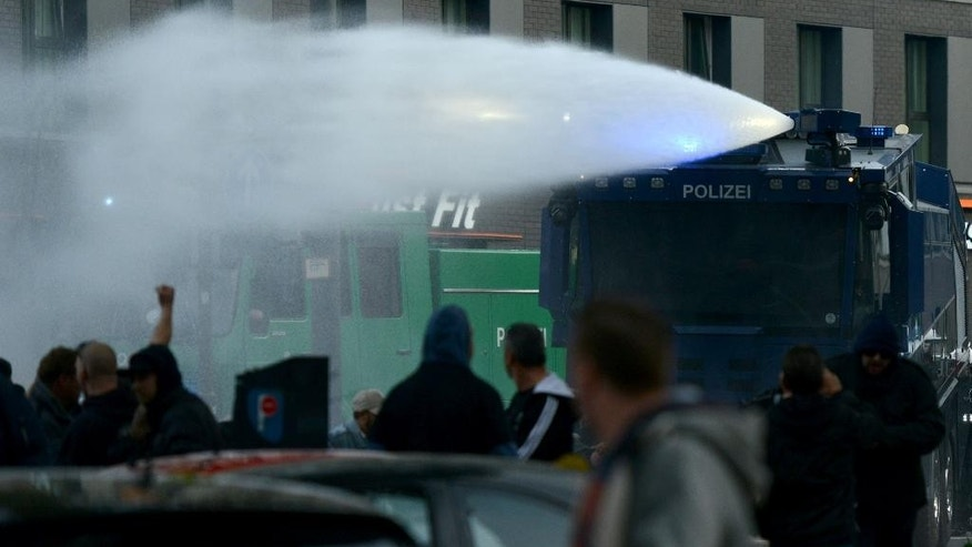 A water canon sprays on demonstrators   in Cologne, Germany,  Sunday Oct. 26, 2014.  A demonstration by German far-right groups has erupted into violence in the heart of the western city of Cologne. Police say they are using water cannons and pepper spray in an attempt to calm the situation after protesters threw bottles and fireworks at officers. Police spokesman Andre Fassbender says there are no figures on injuries or arrests yet. Some 2,000 people attended the demonstration Sunday directed against Islamic extremism. It was organized by neo-Nazi groups and members of Germany's football hooligan scene.(AP Photo/dpa,Caroline Seidel)