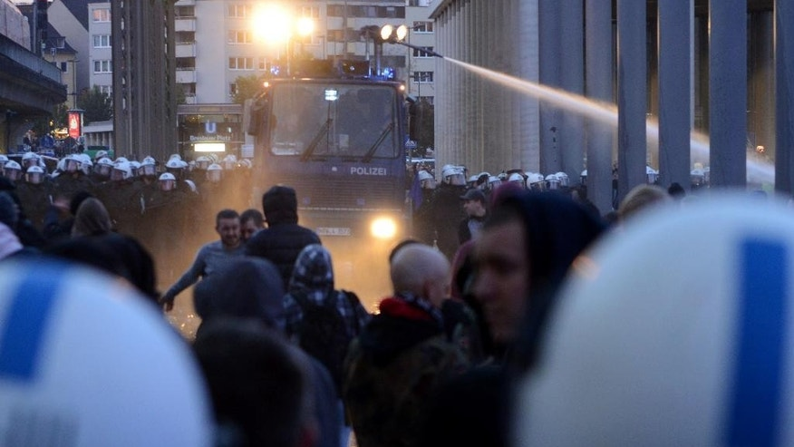 A water canon  is used against demonstrators   in Cologne, Germany, Sunday Oct. 26, 2014.  A demonstration by German far-right groups has erupted into violence in the heart of the western city of Cologne. Police say they are using water cannons and pepper spray in an attempt to calm the situation after protesters threw bottles and fireworks at officers. Police spokesman Andre Fassbender says there are no figures on injuries or arrests yet. Some 2,000 people attended the demonstration Sunday directed against Islamic extremism. It was organized by neo-Nazi groups and members of Germany's football hooligan scene.(AP Photo/dpa,Caroline Seidel)