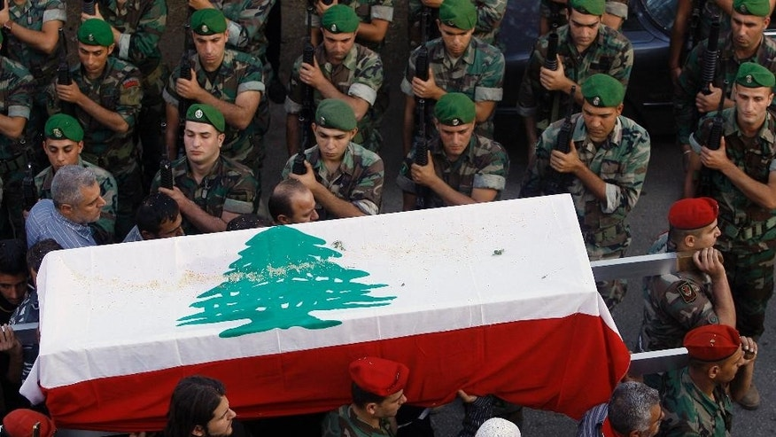 Lebanese army soldiers carry the coffin, wrapped in the national flag, of Lebanese soldier Mohammed Ali Yaseen, who was killed Saturday in a clash with Islamic Militants in Tripoli, during his funeral procession in the southern village of Kfar Tibnit, Lebanon, Sunday, Oct. 26, 2014. Lebanese army tanks pounded Muslim militants' positions in the narrow streets of a poor neighborhood in this northern city Sunday, where fighting has intensified and spread to nearby areas where gunmen killed several soldiers. (AP Photo/Mohammed Zaatari)