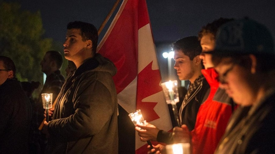 People attend a candlelight vigil at the Tomb of the Unknown Soldier at the National War Memorial in tribute of Cpl. Nathan Cirillo, 24, a reservist from Hamilton, Ontario, who was killed on Wednesday while guarding the tomb by a gunman, in Ottawa on Saturday, Oct. 25, 2014. (AP Photo/The Canadian Press, Justin Tang)