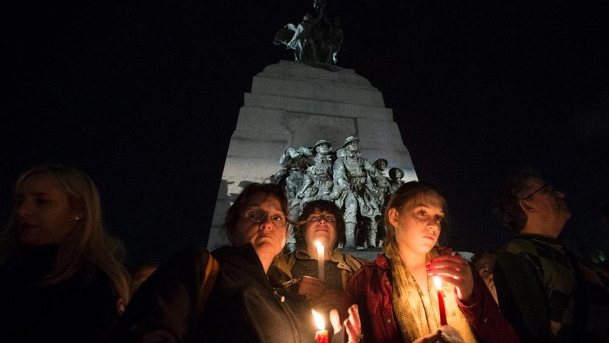 People attend a candlelight vigil at the Tomb of the Unknown Soldier at the National War Memorial in tribute of Cpl. Nathan Cirillo, 24, in Ottawa on Saturday, Oct. 25, 2014. (AP Photo/The Canadian Press, Justin Tang)