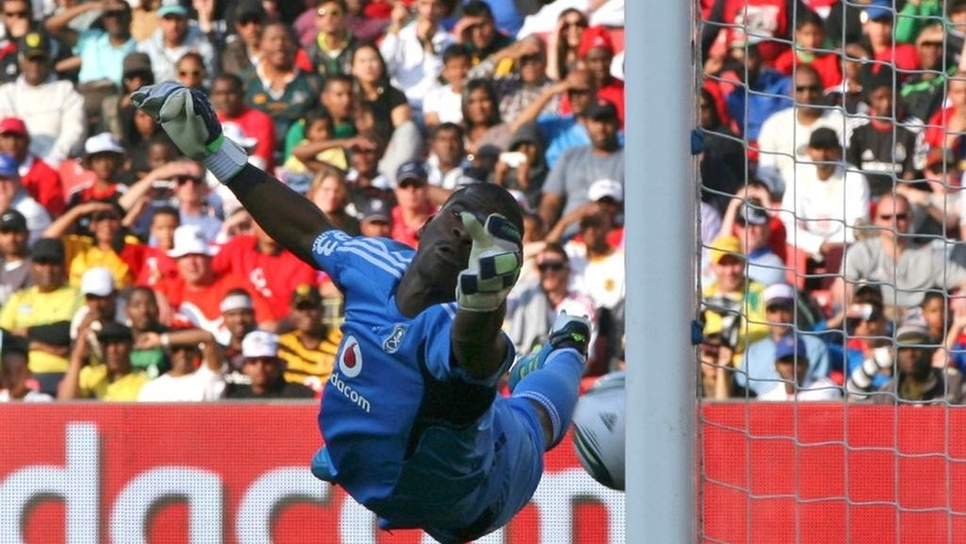 FILE- In this file photo dated Saturday July 23, 2011, Orlando Pirates goalkeeper Senzo Meyiwa dives but fails to stop the ball going below his hand, from a free kick by Tottenham Hotspur Rafael Van der Vaart, during the 2011 Vodacom Challenge at Ellis Park stadium in Johannesburg, South Africa. According to reports Sunday Oct. 26, 2014, soccer club Orlando Pirates says 27-year old South Africa goalkeeper Senzo Meyiwa died during a shooting incident in South Africa. (AP Photo/Themba Hadebe, FILE)