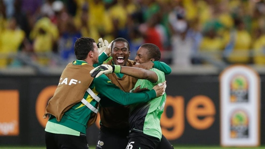 FILE- In this file photo dated Sunday, Jan. 27, 2013, South Africa's goalkeeper Itumeleng Khune, right, celebrates with fellow goalkeepers Wayne Sandilands, left, and Senzo Meyiwa, center, after drawing with Morocco to advance to the quarterfinals of the African Cup of Nations, in Durban, South Africa.  According to reports Sunday Oct. 26, 2014, soccer club Orlando Pirates says 27-year old South Africa goalkeeper Senzo Meyiwa died during a shooting incident in South Africa. (AP Photo/Rebecca Blackwell, FILE)
