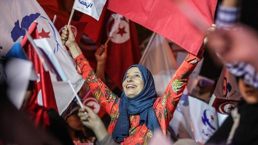 In this photo taken Friday, Oct. 24, 2014, a supporter of the moderate Islamist Ennahda Party waves party flags during a campaign rally in Tunis. Tunisians vote Sunday to elect a permanent parliament and complete a democratic transition that began when they overthrew their long-ruling dictator in 2011. (AP Photo/Aimen Zine)