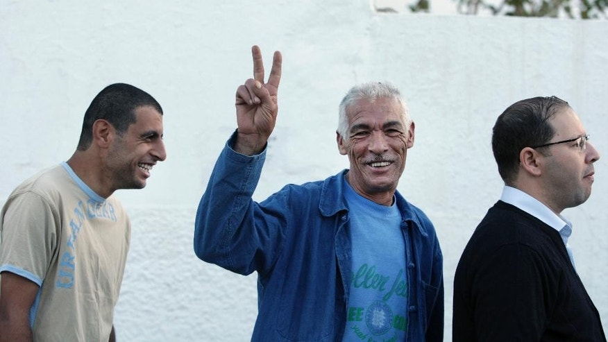 A Tunisian flashes a v-sign as he waits to vote at the entrance to a polling station in Ben Arous, a city south of Tunis, Sunday Oct. 26, 2014. Tunisians lined up Sunday to choose their first five-year parliament since they overthrew their dictator in the 2011 revolution that kicked off the Arab Spring. (AP Photo/Aimen Zine)