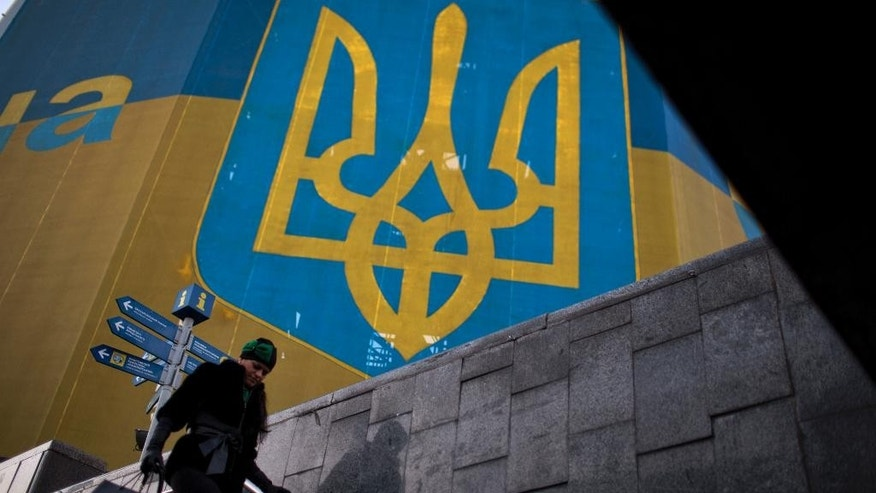 A woman walks past a huge Ukrainian flag the day before of the parliamentary elections in central Kiev, Ukraine, Saturday, Oct. 25, 2014. Parliamentary elections on Sunday in Ukraine promise to usher in a fresh class of politicians, but for millions of Ukrainians change is no promise of improvement. (AP Photo/Emilio Morenatti)