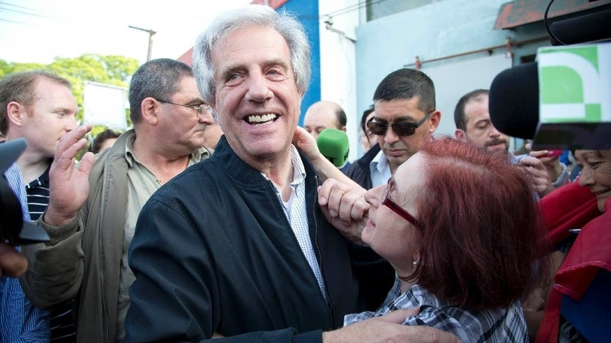 Presidential candidate for the ruling Broad Front party Tabare Vazquez, left, embraces a follower after casting his vote during general elections in Montevideo, Uruguay, Sunday, Oct. 26, 2014. Uruguay's presidential election is set to go into a runoff as undecided voters could opt for change on Sunday, despite an economic boom and social reforms led by the ruling Broad Front coalition. (AP Photo/Natacha Pisarenko)