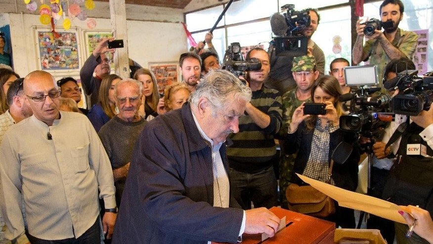 Uruguay's President Jose Mujica casts his vote during general elections in Montevideo, Uruguay Sunday, Oct. 26, 2014. Uruguay's presidential election is set to go into a runoff as undecided voters could opt for change on Sunday, despite an economic boom and social reforms led by the ruling Broad Front coalition. (AP Photo/Natacha Pisarenko)