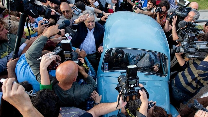 Uruguay's President Jose Mujica, center, leaves after casting his vote during general elections in Montevideo, Uruguay Sunday, Oct. 26, 2014. Uruguay's presidential election is set to go into a runoff as undecided voters could opt for change on Sunday, despite an economic boom and social reforms led by the ruling Broad Front coalition. (AP Photo/Natacha Pisarenko)