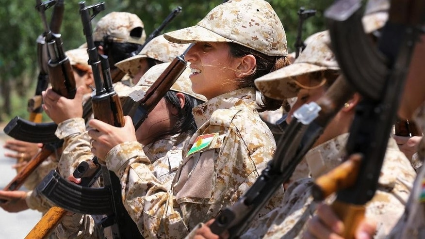 In this Thursday, July 3, 2014 photo, an elite unit of women Kurdish Peshmerga fighters trains in Sulaimaniyah, 160 miles (260 kilometers) northeast of Baghdad, Iraq. Among the Kurdish fighters defending the Syrian town of Kobani against the IS are thousands of women. In April, Kurdish fighters created all-female combat units that have grown to include more than 10,000 women who played a major role in battles against IS, said Nasser Haj Mansour, a defense official in Syria's Kurdish region. (AP Photo)