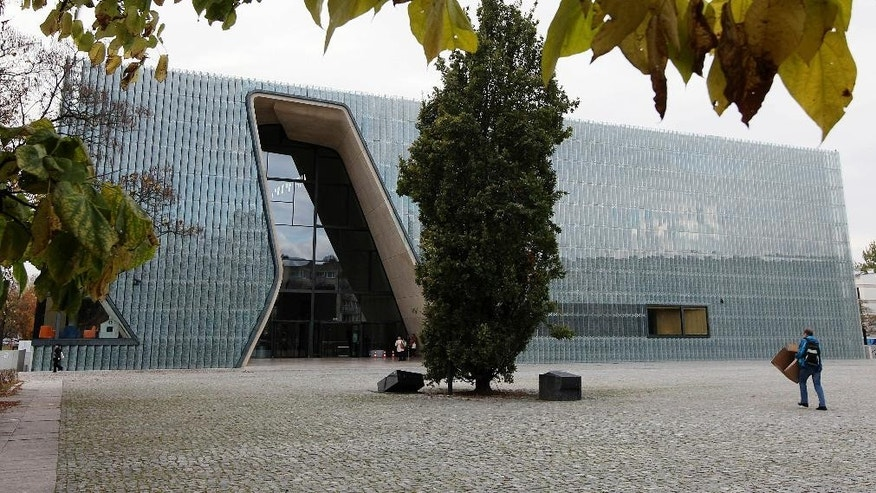 In this photo taken Tuesday, Oct. 21, 2014, a person walks outside the POLIN Museum of the History of Polish Jews in Warsaw, Poland. The museum, which opened in 2013 for temporary exhibitions and cultural programs, is holding the grand opening Tuesday, Oct. 28, 2014, for its core exhibition, the heart of the museum. The exhibition tells the 1,000 year history of Jews in Poland, from the Middle Ages until today. (AP Photo/Czarek Sokolowski)
