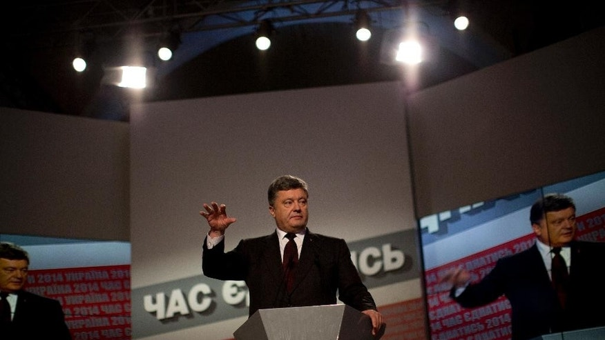 Ukrainian President Petro Poroshenko gestures during a press conference following the parliamentary elections in Kiev, Ukraine, Sunday, Oct. 26, 2014. Exit polls indicate Ukrainians have overwhelmingly voted for several pro-Western parties in a landmark parliamentary election Sunday, although a coalition parliament seems to be likely.  (AP Photo/Emilio Morenatti)
