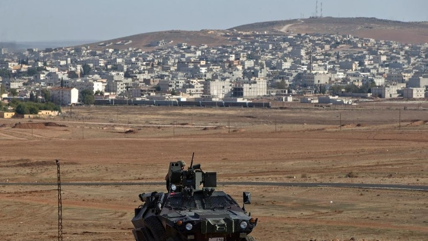 Oct. 26, 2014: A Turkish military vehicle is backdropped by the Syrian town of Kobani, on a hilltop on the outskirts of Suruc, Turkey, near the Turkey-Syria border. (AP)