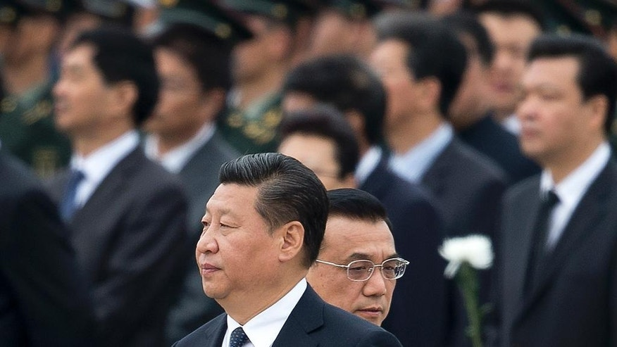 FILE - In this file photo taken Tuesday, Sept. 30, 2014, Chinese Premier Li Keqiang, right, walks past Chinese President Xi Jinping as they arrive at the Monument to the People's Heroes during a ceremony marking Martyr's Day at Tiananmen Square in Beijing, China. Afghan President Ashraf Ghani Ahmadzai travels to China on Tuesday, Oct. 28, signaling the pivotal role he hopes Beijing will play in Afghanistan's future, not only in the economic reconstruction of his war-ravaged country after U.S. and allied combat troops leave by the end of the year but also in a strategic foreign policy aimed at building peace across a region long riven by mistrust and violence. (AP Photo/Andy Wong, File)