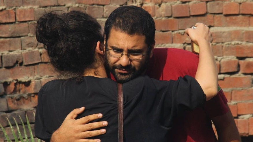 Egypt's most prominent activist Alaa Abdel-Fattah receives a hug from a supporter outside a court that convicted 23 activists of staging an illegal demonstration and sentenced them each to three years in jail, in Cairo, Egypt, Sunday, Oct. 26, 2014. Among the 23 is Sanaa Seif, who hails from a family of longtime rights campaigners, including her late father Ahmed Seif al-Dawla and brother Alaa Abdel-Fattah. Another defendant is Yara Sallam, a prominent rights lawyer. Sunday's verdicts, which can be appealed, comes at a time when Egypt is swept by nationalist sentiments following a dramatic surge in attacks blamed on Islamic militants on troops and security forces in the Sinai Peninsula while witnessing a smear campaign targeting many of the secular pro-democracy campaigners behind the 2011 uprising. (AP Photo/Mohammed Abu Zeid)