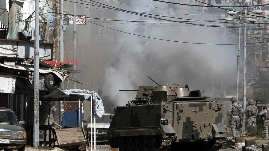 Lebanese army soldiers stand beside an armored vehicle during clashes with Islamic militants in the northern port city of Tripoli, Lebanon, Sunday, Oct. 26, 2014. The Lebanese army brought tanks and commando forces into the northern city of Tripoli Sunday, where fighting with Muslim militants has intensified and spread to nearby areas. (AP Photo/Bilal Hussein)