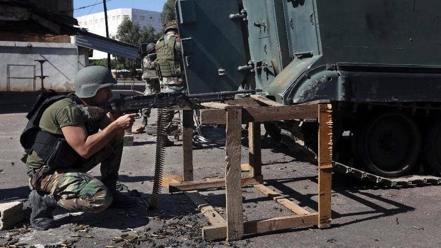 A Lebanese army soldier opens fire with spent bullet casings on the ground during clashes with Islamic militants in the northern port city of Tripoli, Lebanon, Sunday, Oct. 26, 2014. The Lebanese army brought tanks and commando forces into the northern city of Tripoli Sunday, where fighting with Muslim militants has intensified and spread to nearby areas. (AP Photo/Bilal Hussein)
