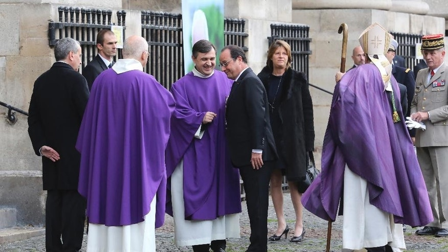 French President Francois Hollande, center, arrives at a funeral service for former Total SA Chief Executive Christophe de Margerie  at Saint Sulpice church in Paris, France, Monday, Oct. 27, 2014. Margerie and three French crew members were killed Oct. 20, when the business jet they were in clipped an airport snowplow on takeoff at Moscow's Vnukovo airport, crashed and burst into flames. (AP Photo/Remy de la Mauviniere)