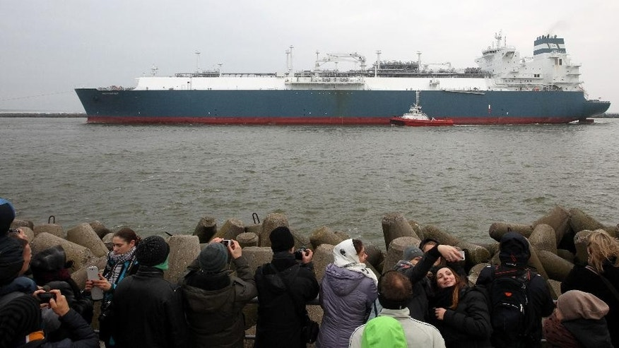"People take photographs as ""Independence"", a Liquefied Natural Gas (LNG) storage vessel is maneuvered by tugboats through the sea gate port of Klaipeda, Lithuania, Monday, Oct. 27, 2014. The floating natural gas terminal arrived in the Lithuanian port of Klaipeda, in a move by the Baltic country to further reduce its reliance on energy supplies from Russia. (AP Photo/Kestutis Vanagas)"