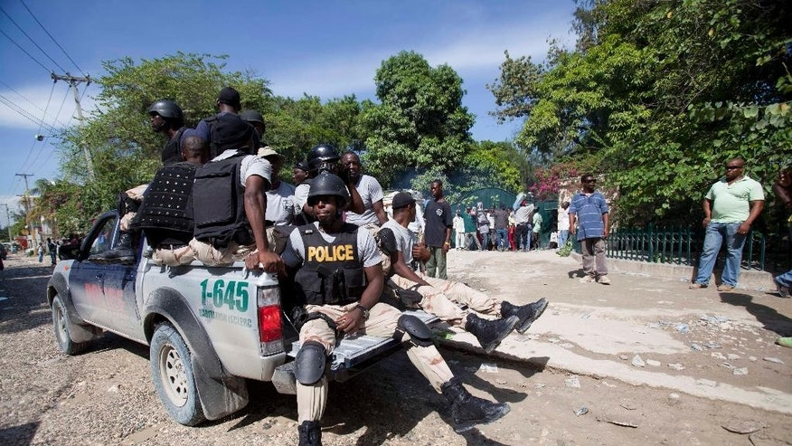 FILE - In this Friday, Oct. 10, 2014 file photo, national police officers patrol in front of the home of Haiti's former President Jean-Bertrand Aristide while his supporters rally outside his home in Port-au-Prince, Haiti. Police have been stationed outside the cement-block walls of his compound for sweeks, keeping watch and awaiting orders to carry out an arrest warrant issued by a judge investigating allegations of corruption, drug trafficking and money laundering that date back nearly a decade. The warrant was issued for failure to appear to testify in a closed evidence-gathering session in August. (AP Photo/Dieu Nalio Chery, File)