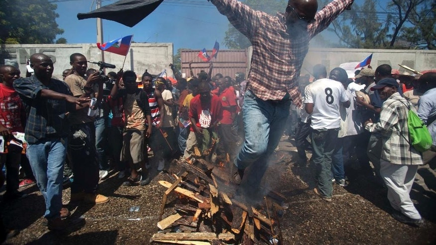 FILE - In this Sept. 30, 2014 file photo, a supporter of former Haitian President Jean-Bertrand Aristide walks over burning wood pile as part of a voodoo ceremony, on the anniversary of the 1991 military coup that ousted Aristide, in Port-au-Prince, Haiti. As rumors have circulated that Aristide's arrest was imminent, supporters of the twice-elected, twice-deposed president continue to rally outside his compound near downtown Port-au-Prince. A warrant for his arrest was issued for failure to appear to testify in a closed evidence-gathering session in August. (AP Photo/Dieu Nalio Chery, File)