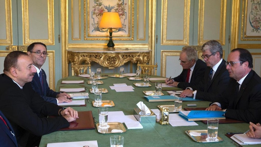 French President Francois Hollande, right,, sits across from Azerbaijan's President Ilham Aliyev during talks at the Elysee Palace in Paris, Monday, Oc. 27, 2014.  Aliev and his Armenian counterpart Serge Sarkisian are expected to meet in Paris to discuss the situation over the South Caucasus region Nagorno-Karabakh. (AP Photo/Philippe Wojazer, Pool)