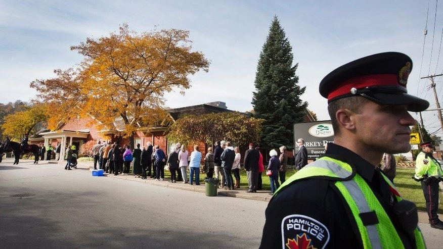 Hamilton police control the scene as people wait in line to sign the book of condolences and attending the public visitation for Cpl Nathan Cirillo at the Markey-Dermody Funeral Home in Hamilton, Ontario on Monday, Oct. 27, 2014. Cirillo, the 24-year-old reservist with the Argyll and Sutherland Highlanders of Canada, was gunned down Oct. 22 as he stood ceremonial guard at the National War Memorial in Ottawa. (AP Photo/The Canadian Press, Peter Power)