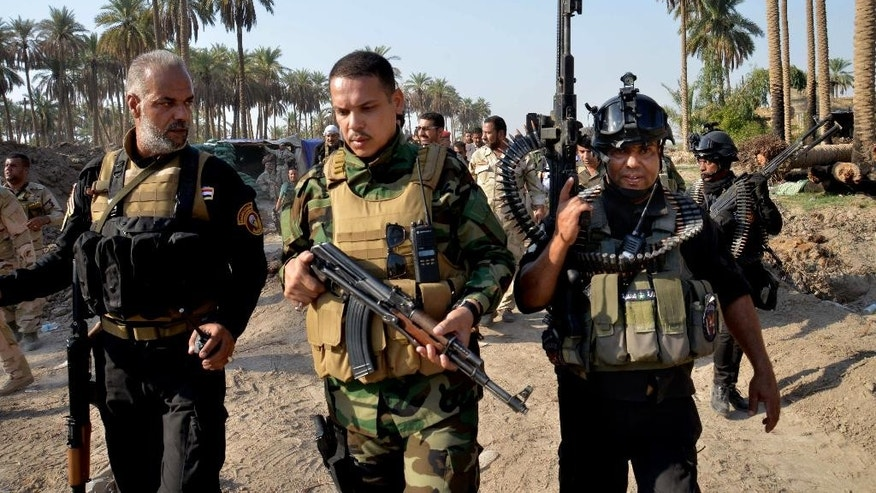 Oct. 25, 2014: In this photo, Iraqi security forces hold their weapons as they patrol Jurf al-Sakhar, 43 miles south of Baghdad, Iraq. (AP)