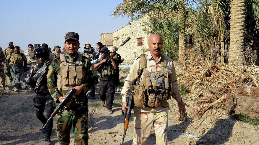In this Saturday, Oct. 25, 2014 photo, Iraqi security forces and Shiite militiamen patrol Jurf al-Sakhar, 43 miles (70 kilometers) south of Baghdad, Iraq. Iraqi soldiers backed by Shiite militiamen retook control Sunday, Oct. 26, 2014 of a Sunni town seized previously by Islamic militants, said an Iraqi official and state-run TV, a rare victory for Iraqi security forces that have been battling to regain areas lost to the militants. (AP Photo)