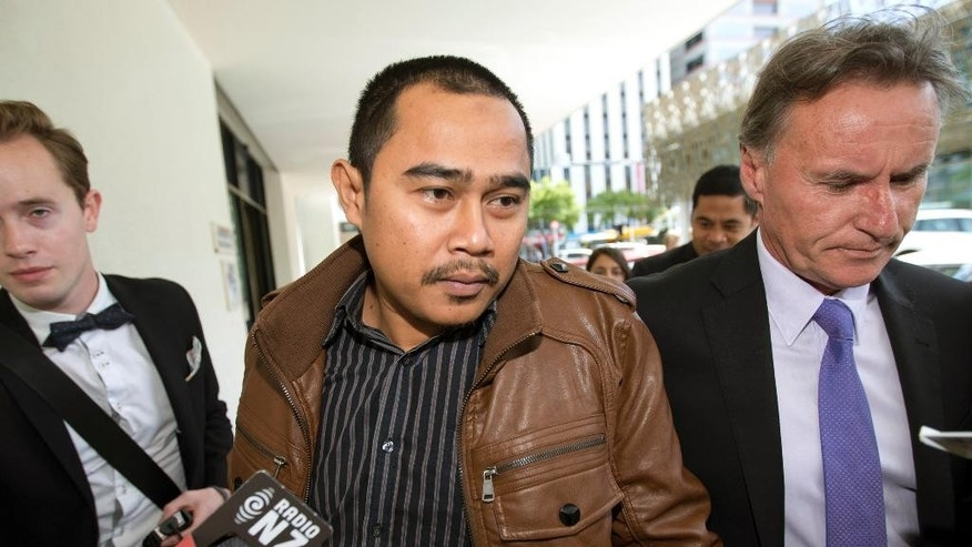 Malaysian diplomat  Muhammad Rizalman Ismail  is ushered to a waiting taxi after his appearance at the Wellington District Court in New Zealand, on Tuesday, Oct. 28, 2014. Rizalman was extradited to New Zealand last week after earlier leaving the country under the protection of diplomatic immunity. Rizalman has been charged with burglary and assault with the intent to rape in a case that has proved to be diplomatically embarrassing for both Malaysia and New Zealand.(AP Photo/New Zealand Herald, Mark Mitchell  AUSTRALIA OUT, NEW ZEALAND OUT