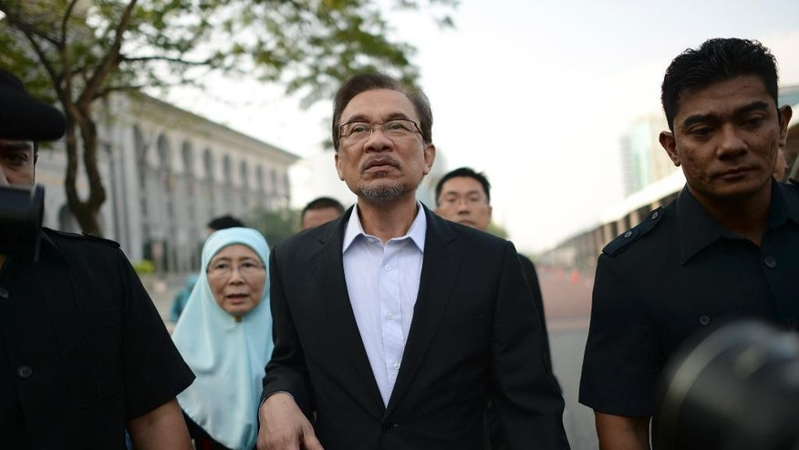 Malaysian opposition leader Anwar Ibrahim, center, walks with his wife Wan Azizah as they arrive for his final hearing of his sodomy conviction in Putrajaya, Malaysia, Tuesday, Oct. 28, 2014. Anwar was found guilty by the Malaysian Court of Appeal on March 7, 2014 of having sodomized his former aide Mohd Saiful Bukhari Azlan, 27. (AP Photo)