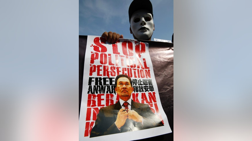 A supporter holds a poster of Malaysian opposition leader Anwar Ibrahim during his final hearing of his sodomy conviction in Putrajaya, Malaysia, Tuesday, Oct. 28, 2014. Anwar was found guilty by the Malaysian Court of Appeal on March 7, 2014 of having sodomized his former aide Mohd Saiful Bukhari Azlan, 27.  (AP Photo/Vincent Thian)
