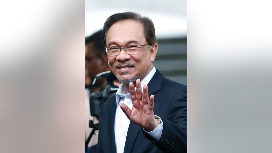 Malaysian opposition leader Anwar Ibrahim waves as he arrives for his final hearing of his sodomy conviction in Putrajaya, Malaysia, Tuesday, Oct. 28, 2014. Anwar was found guilty by the Malaysian Court of Appeal on March 7, 2014 of having sodomized his former aide Mohd Saiful Bukhari Azlan, 27.  (AP Photo/Vincent Thian)