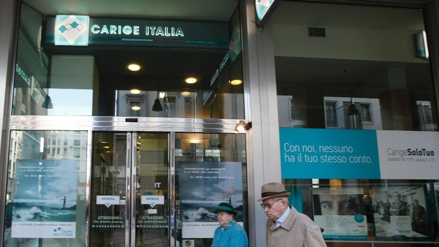 "People walk past a ""Banca Carige"" bank branch in Milan, Italy, Sunday, Oct.26, 2014. The European Central Bank says 13 of Europe's 130 biggest banks have flunked an in-depth review of their finances and need an extra 10 billion euros ($12.5 billion) to cushion themselves against any future crises. ECB officials said Sunday the test had been tougher than similar reviews in 2011 and 2010, which gave a pass to banks that later needed bailouts. (AP Photo/Luca Bruno)"