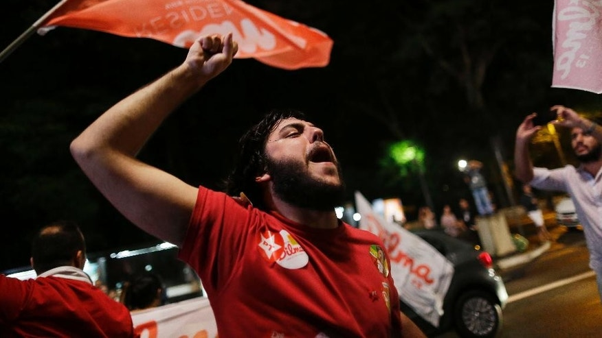 A supporters of presidential candidate Dilma Rousseff, celebrates her electoral victory in Sao Paulo, Brazil, Sunday, Oct. 26, 2014. Official results showed Sunday that President Rousseff defeated opposition candidate Aecio Neves of the Brazilian Social Democracy Party, and was re-elected Brazil's president. (AP Photo/Nelson Antoine)