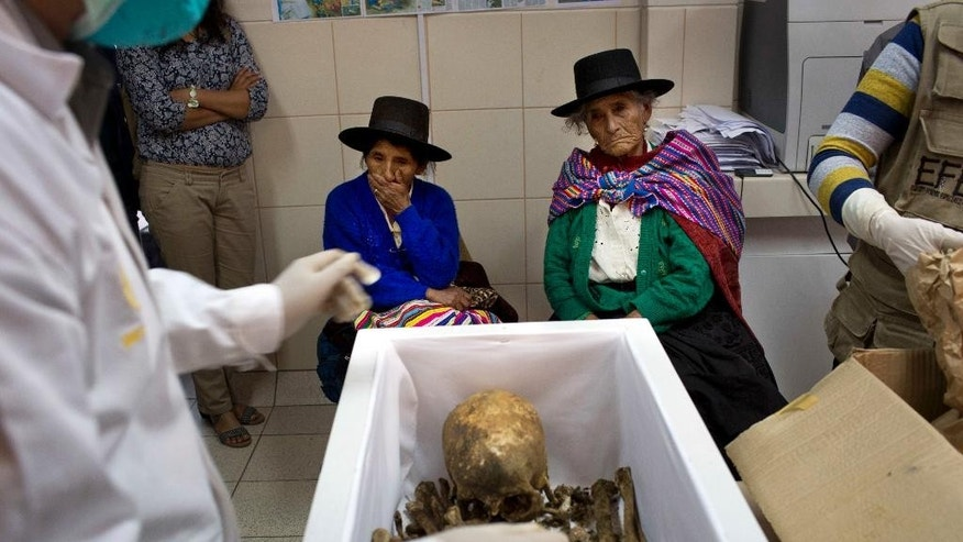 Dionisia Huamani Quispe, left center, and Eusebia Palomino Arome, right center, witness how forensic anthropologists arrange in a coffin the remains of their relatives, slain three decades ago during the country's dirty war, in a forensic laboratory in Huamanga, Peru, Sunday, Oct. 26, 2014. Hundreds arrived in the Ayacucho state capital for Monday's handover of 80 sets of remains. Simple white coffins bore the bones of fathers, mothers, wives, children and brothers. Forensic teams have been exhuming victims of Peru's 1980-2000 internal conflict since 2006, recovering 2.925 sets of remains. (AP Photo/Rodrigo Abd)