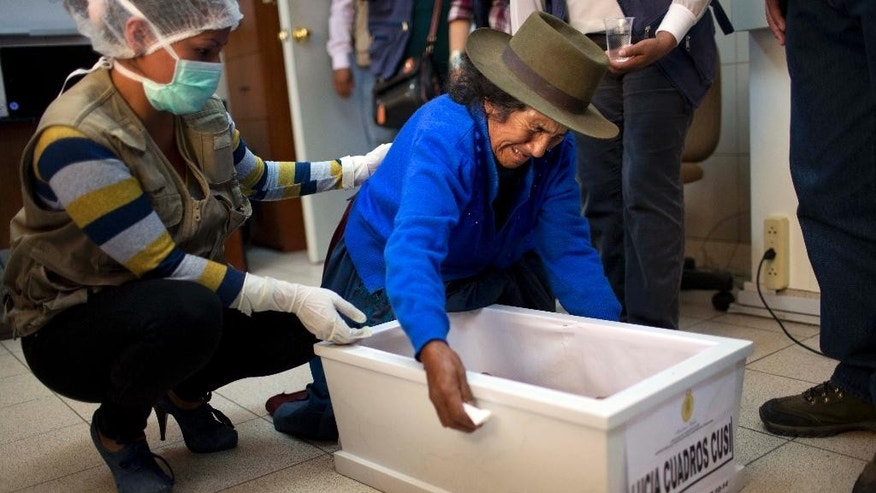 Angelica Cusi Diaz cries over the coffin that contains the remains of her daughter Lucia Cuadros, who was pregnant when slain three decades ago during Peru's dirty war, in a forensic laboratory in Huamanga, Peru, Sunday, Oct. 26, 2014. Hundreds of small farmers came from remote mountains and jungle valleys to receive the exhumed remains of their loved ones. Simple white coffins bore the bones of fathers, mothers, wives, children and brothers. Forensic teams have been exhuming victims of Peru's 1980-2000 internal conflict since 2006, recovering 2.925 sets of remains. (AP Photo/Rodrigo Abd)