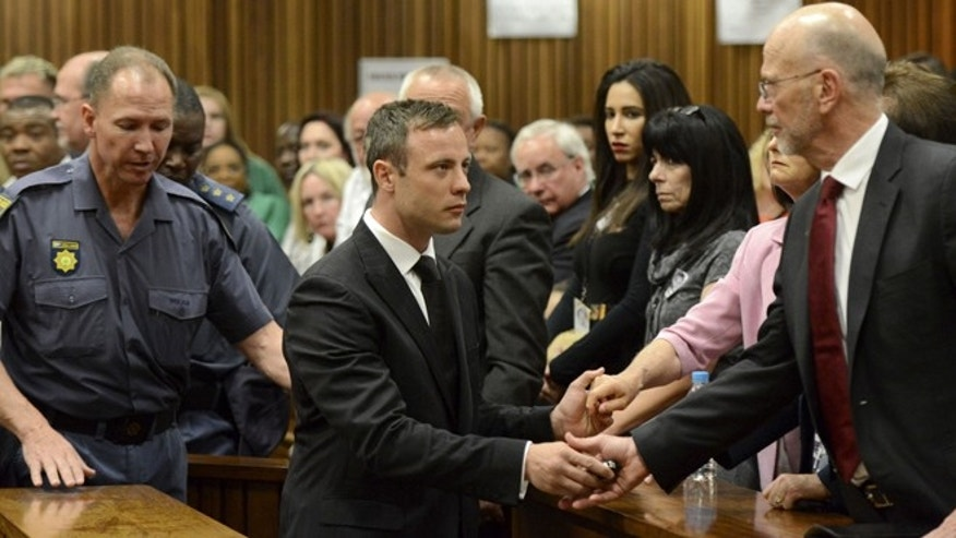 Oct. 21, 2014: Oscar Pistorius, center, greets his uncle Arnold Pistorius, right, and other family members as he is led down to the cells of the court in Pretoria, South Africa. Pistorius received a five-year prison sentence for culpable homicide by judge Thokozile Masipais for the killing of his girlfriend Reeva Steenkamp last year