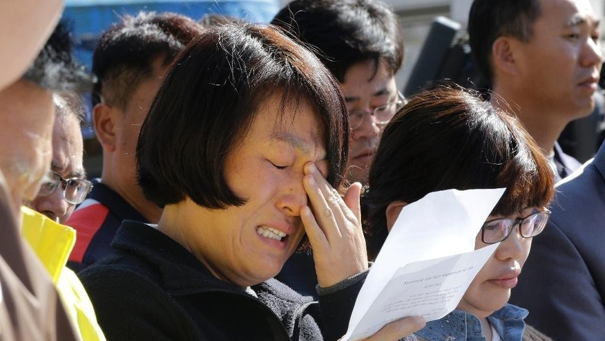 An unidentified family member of passengers aboard the sunken ferry Sewol caries as she demands maximum punishment to be sentenced on the crew members of the ferry during their trial at Gwangju District Court in Gwangju, South Korea, Monday, Oct. 27, 2014. South Korean prosecutors demanded the death penalty for the captain of a doomed ferry and life sentences to three key crew members, arguing Monday they are responsible for April's sinking that killed more than 300 people, news reports said. (AP Photo/Ahn Young-joon)