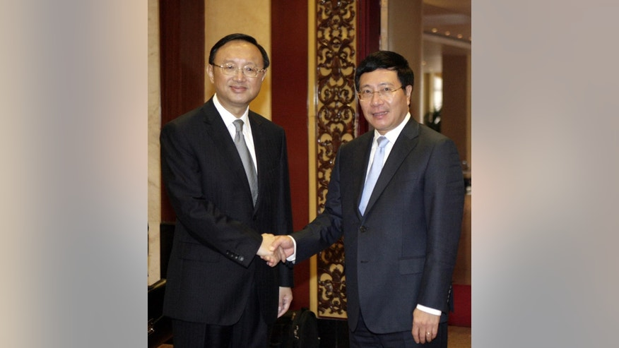 Chinese State Councilor Yang Jiechi, left, shakes hands with Vietnamese Deputy Prime Minister Pham Binh Minh, who is also the Foreign Minister before a meeting on bilateral cooperation in Hanoi, Vietnam Monday Oct. 27, 2014. This is Yang's second visit to Vietnam since June in an effort to ease tension over the maritime disputes between the two communist neighbors whose relations plunged to its lowest point in years following Chinese deployment of an oil rig near the Paracels islands in the South China Sea in May. (AP Phoito/Tran Van Minh)