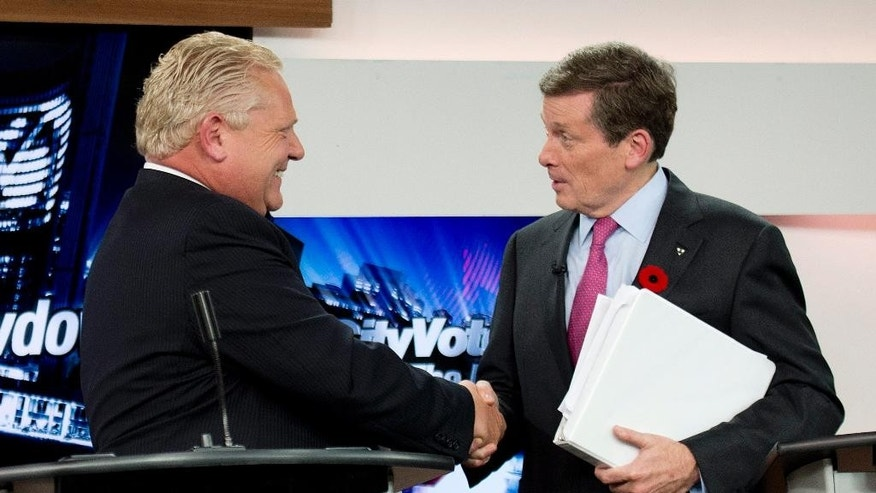 Oct. 23, 2014: In this file photo, Toronto mayoral candidates Doug Ford, left, and John Tory shake hands during the final mayoral debate for the Toronto mayoral race in Toronto. (AP/The Canadian Press, Nathan Denette)