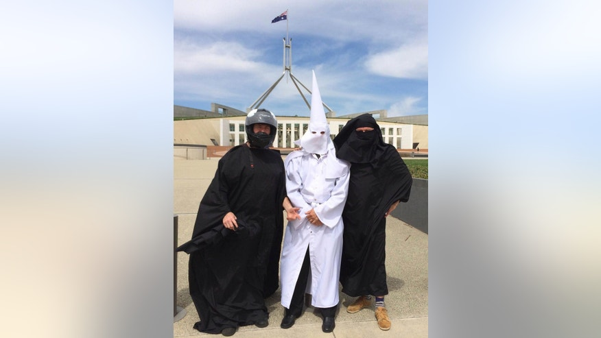 Three men wearing a Ku Klux Klan hood, a niqab and a motorcycle helmet pose for a photo outside Australia's Parliament House in Canberra, Monday, Oct. 27, 2014.  The three men who attempted to enter Australia's Parliament House on Monday said they were unfairly treated under new regulations targeting Muslim face veils. (AP Photo/Nick Folkes)