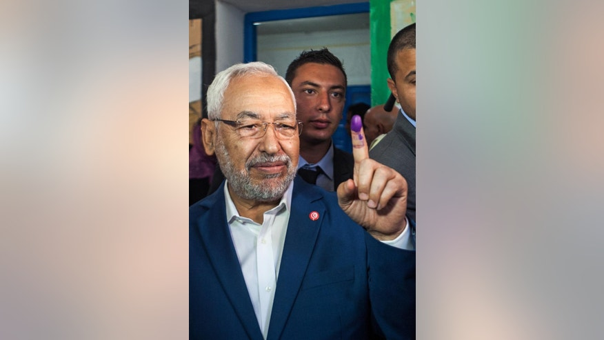 Rachid Ghannouchi, leader of the Tunisian moderate Islamist Ennahda Party, holds up his ink stained finger after voting at a polling station in Ben Arous, Tunisia, Sunday, Oct. 26, 2014. Tunisians expressed tentative hope for the future as they lined up early Sunday to choose their first five-year parliament since they overthrew their dictator in the 2011 revolution that kicked off the Arab Spring. (AP Photo/Aimen Zine)