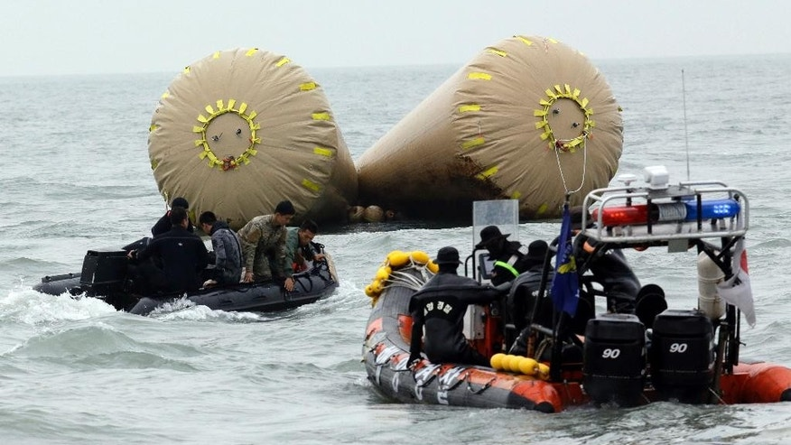 FILE - In this April 19, 2014 file photo, South Korean rescue members search passengers believed to have been trapped in the sunken ferry Sewol near the buoys which were installed to mark the area in the water off the southern coast near Jindo, south of Seoul, South Korea.  The first body found in three months was being recovered Tuesday, Oct. 28, 2014,  from the sunken South Korean ferry, increasing the official death toll to 295, officials said. (AP Photo/Lee Jin-man, File)