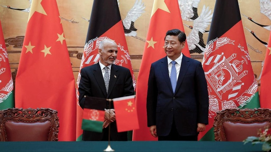 Chinese President Xi Jinping, right, and Afghan President Ashraf Ghani Ahmadzai, left, attend the signing ceremony at the Great Hall of the People Tuesday, Oct. 28, 2014 in Beijing, China.  Afghanistan's new president is visiting Beijing to seek Chinese help in rebuilding his country and boosting regional stability. (AP Photo/Lintao Zhang, Pool)