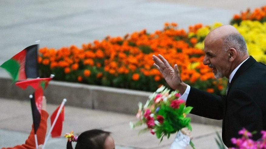 Afghan President Ashraf Ghani Ahmadzai waves to the children waving flags and flowers during a welcome ceremony outside the Great Hall of the People in Beijing, China Tuesday, Oct. 28, 2014. Afghanistan's new president has begun a three-day visit to Beijing that highlights his hopes for a Chinese role in rebuilding the country and boosting regional stability.  (AP Photo/Andy Wong)